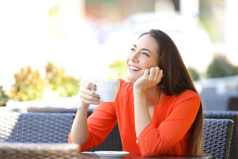 Glad kvinna som tänker dricka kaffe i bar royaltyfria foton