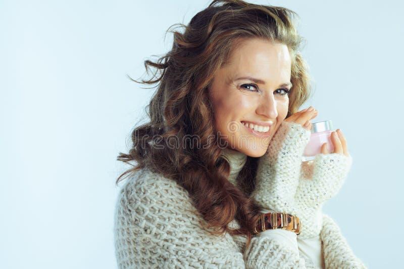 Glad kvinna som visar kallt hudvårdande ansiktskädda royaltyfria foton