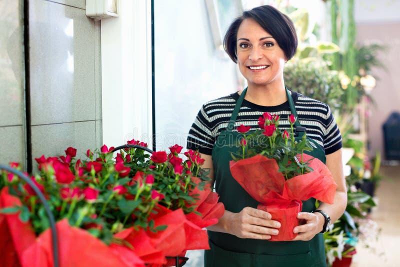 Glad kvinnablomsterhandlare som ler bland de inlagda växterna royaltyfria bilder