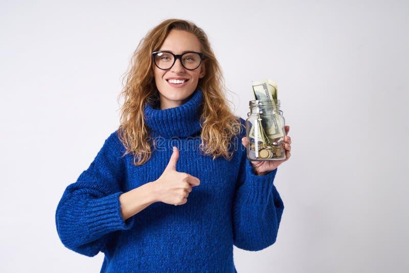 Glad kvinnainnehavspargris och pengar royaltyfria bilder