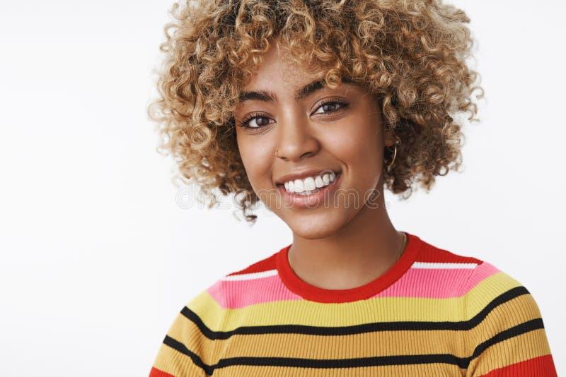Glad kvinnlig student f?r bekymmersl?s och f?rtjust gullig afrikansk amerikan som ler se i huvudsak den fullgjorde kameran och royaltyfri bild