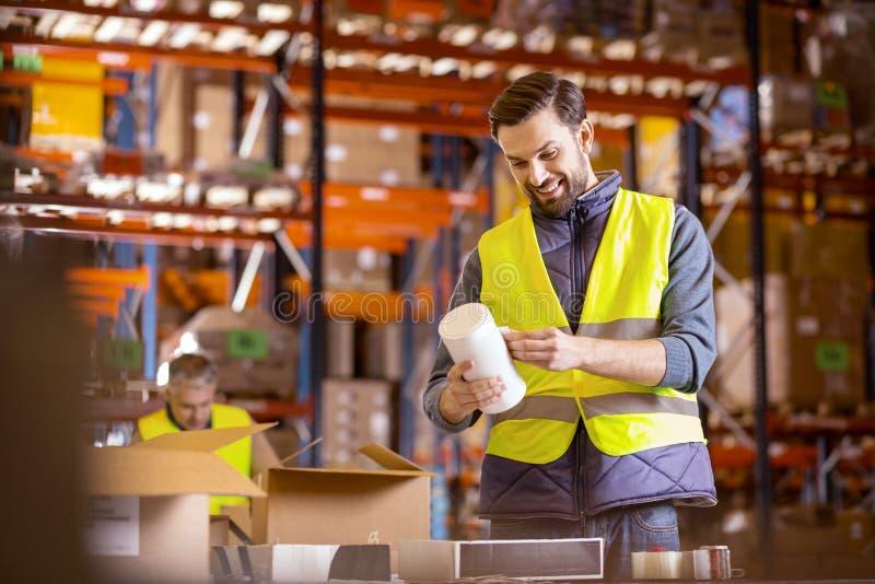 Glad lagerarbetare som sätter klistermärkear royaltyfri foto