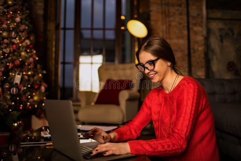 Glad, leende kvinna i modesta glasögon och skickligt slitage Skriva text på den bärbara datorn royaltyfri fotografi