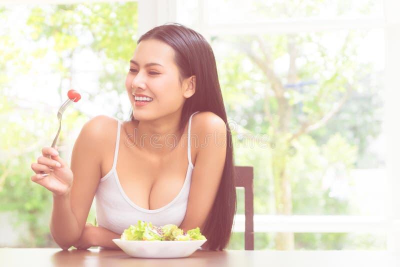 Glad leende kvinna som äter tomat och sallad för friska kroppar och hälsosamma livsmedel arkivfoton