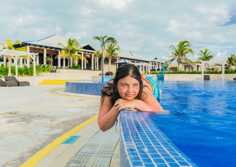 Glad liten flicka som tycker om hennes tid och kopplar av i simbassäng på det guld- tulpanhotellet arkivfoto