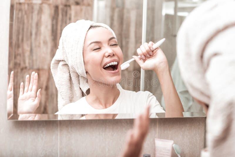 Glad lycklig kvinna som rymmer en tandborste i hennes hand arkivbild