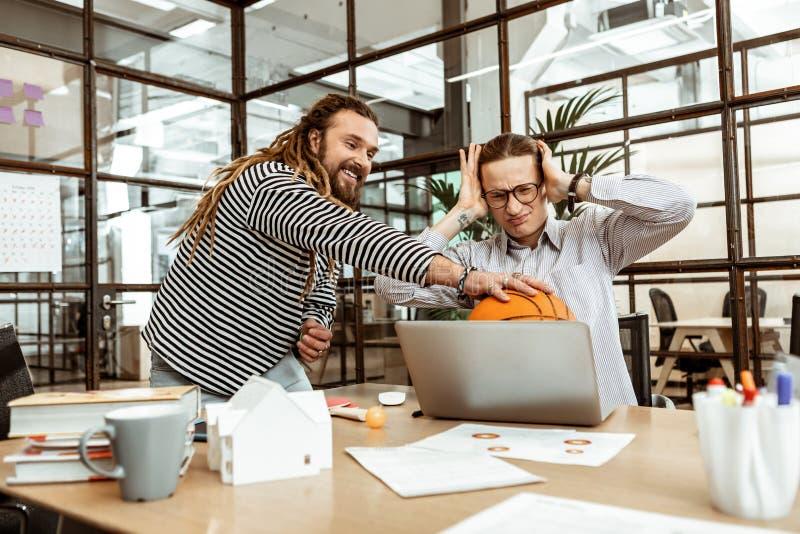 Glad lycklig man som sätter en boll på bärbara datorn arkivbild