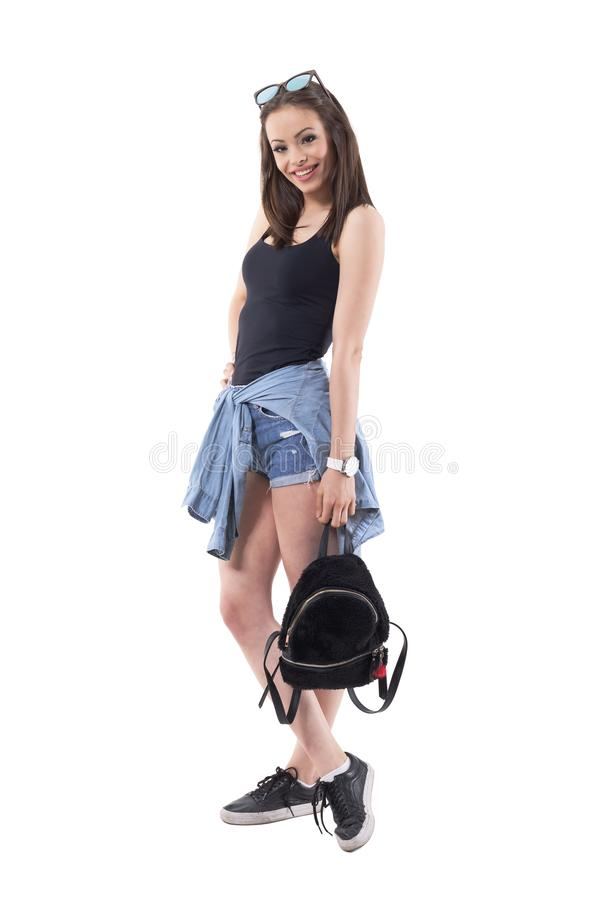 Glad lycklig säker stilfull millennial kvinna som poserar med den svarta fluffiga påsen och solglasögon på huvudet arkivfoto