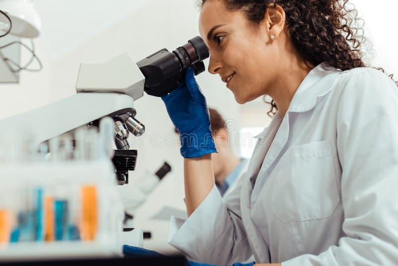 Glad lycklig smart kvinna som använder mikroskopet arkivfoton