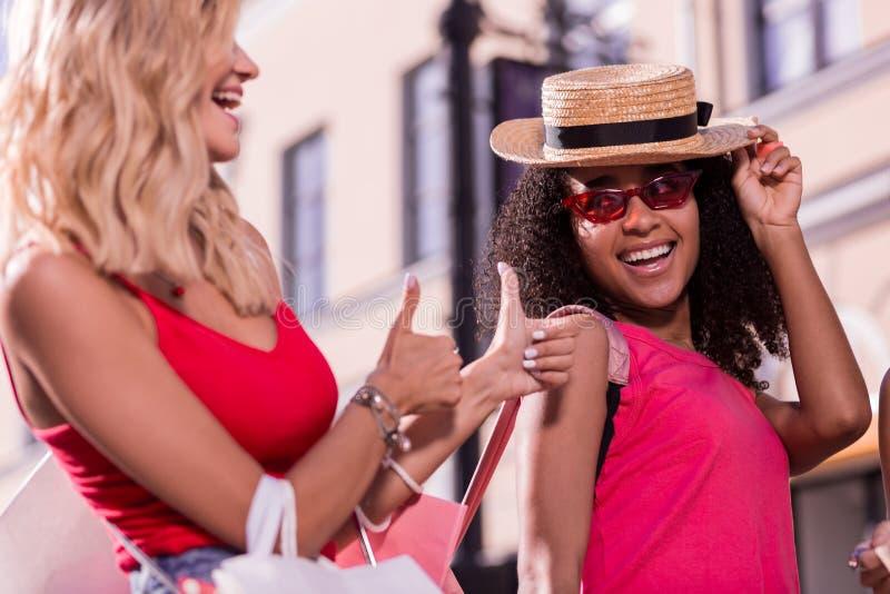 Glad lycklig ung kvinna som visar reko tecken royaltyfria foton