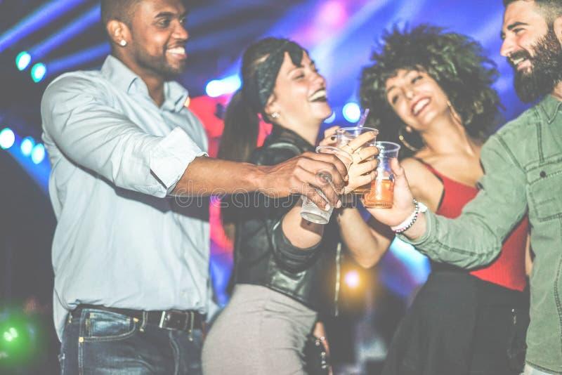Glad mångskiftande kulturvänner som har fest på klubben på natten - ungdomar som har kul med cocktails på discodans golv royaltyfri foto