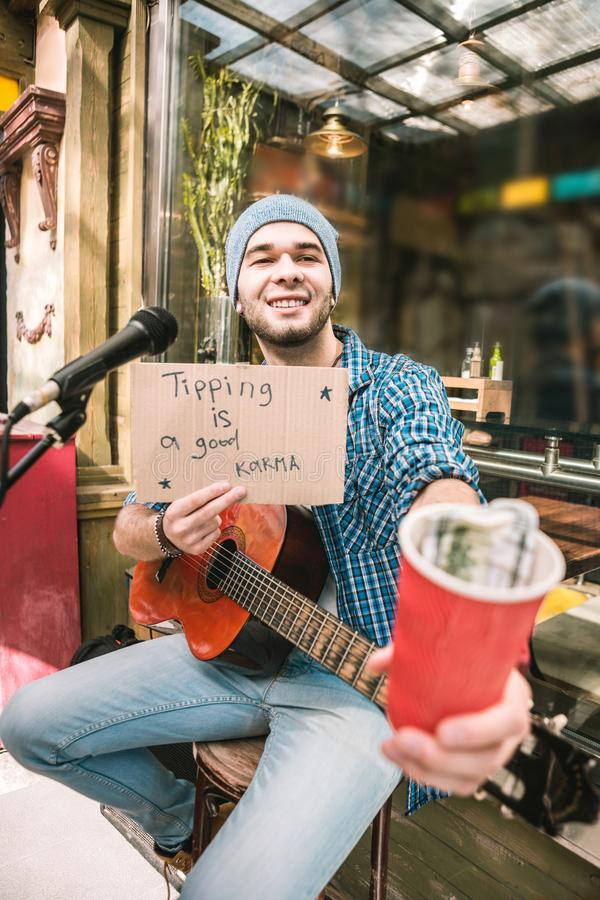 Glad male musician questing about tips after play royalty free stock photography