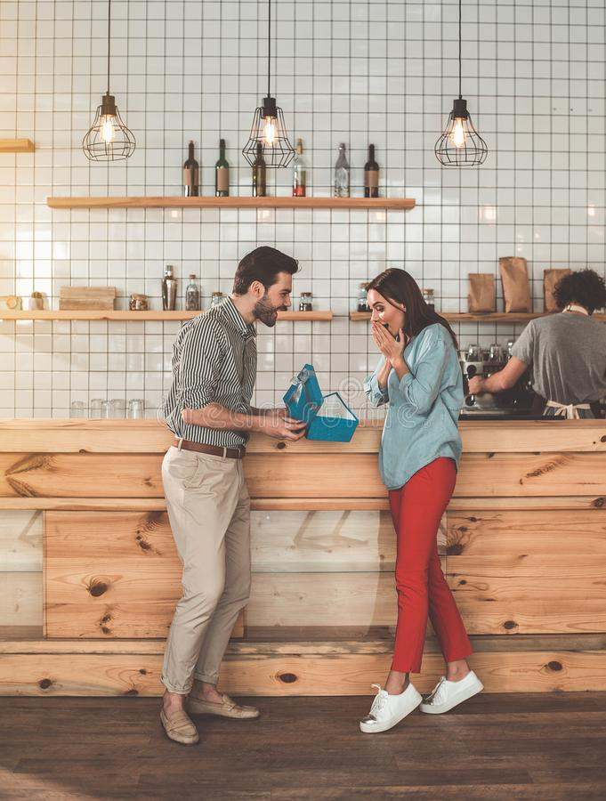 Glad man opening present box in front of girlfriend. This is for you. Excited young women is receiving gift from man. They are standing near counter in coffee stock image