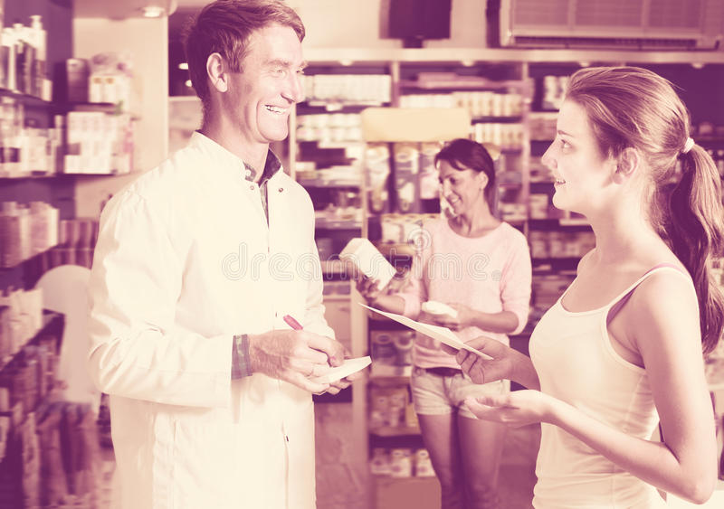 Glad man pharmacist helping customers royalty free stock photography