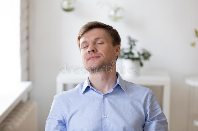 Glad man sitting with close eyes and dreaming. Sleepy man sitting at workplace with close eyes imagine holidays vacation weekend or dreaming about pleasure royalty free stock photography