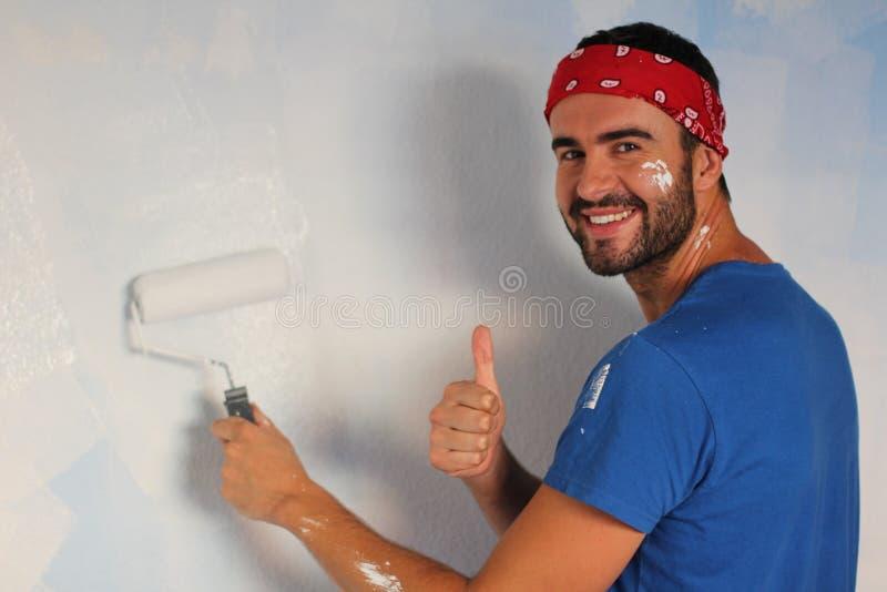 Glad man som målar en vägg med en rulle och ge sig händer upp arkivbilder