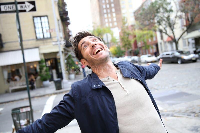 Glad man som uttrycker lycka i stadsgatorna arkivbild