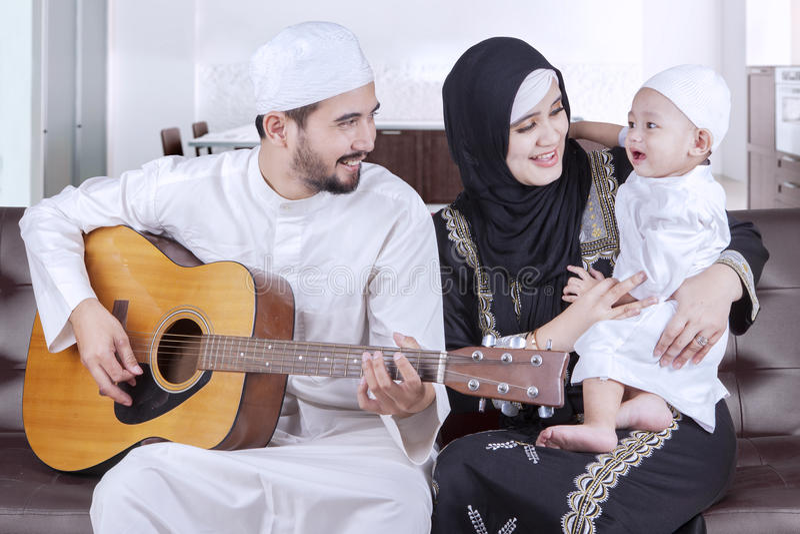 Glad mitt - östlig familj som spelar gitarren royaltyfri fotografi