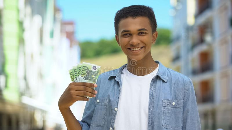 Glad mixed-race young male showing euros bunch and smiling, first salary finance stock photos