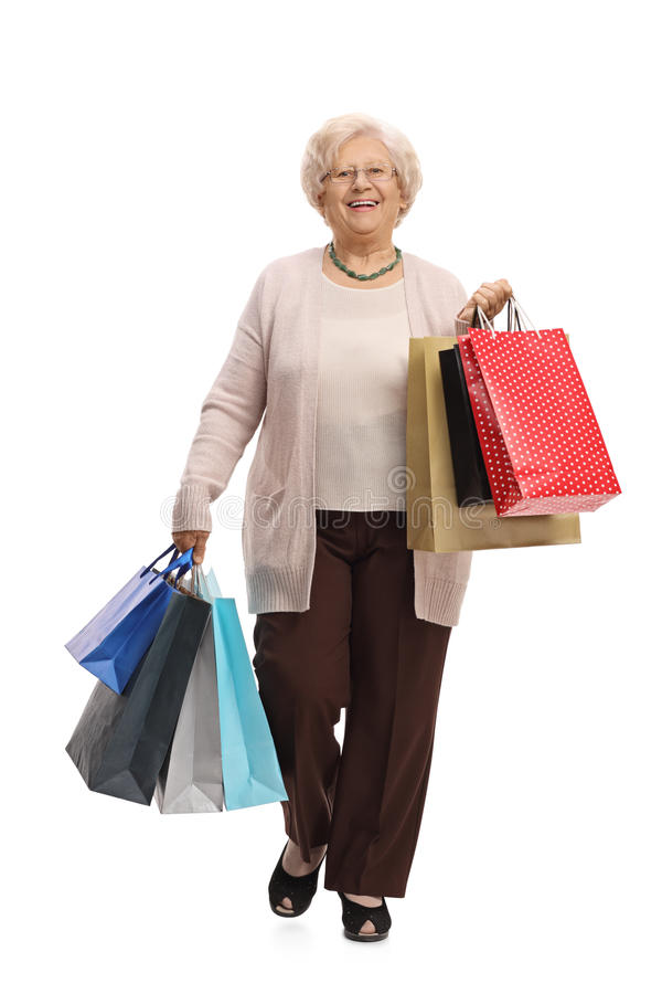 Glad mogen kvinna med shoppingpåsar som går in mot cameren arkivbild