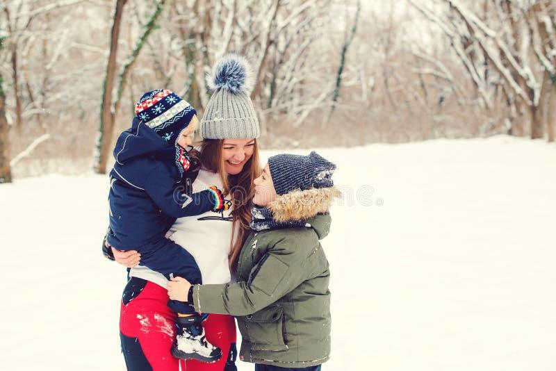 Glad mor kramar sina söta söner, ler och skrattar Winter mode Jul- och vinterhelgdagar Glade barn med mamma på en royaltyfri foto