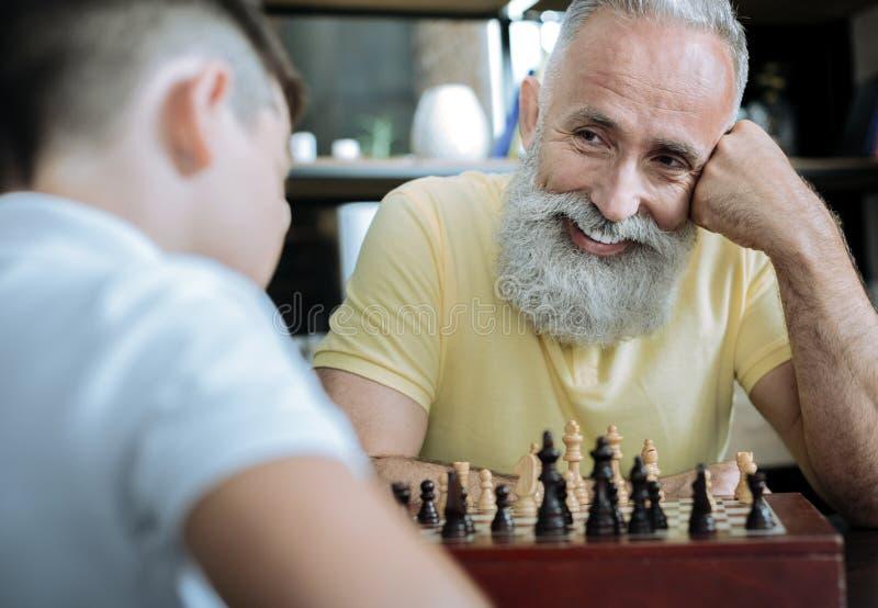 Glad morförälder som strålar, medan spela schack med ungen arkivbilder