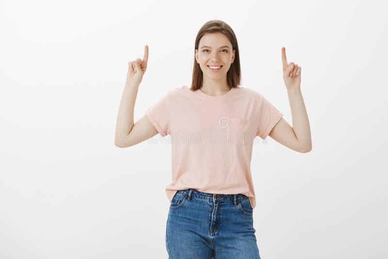 Glad och bekymmerslös härlig kvinna i den tillfälliga dräkten som lyfter händer och pekar upp med pekfingrar som i huvudsak ler arkivfoton