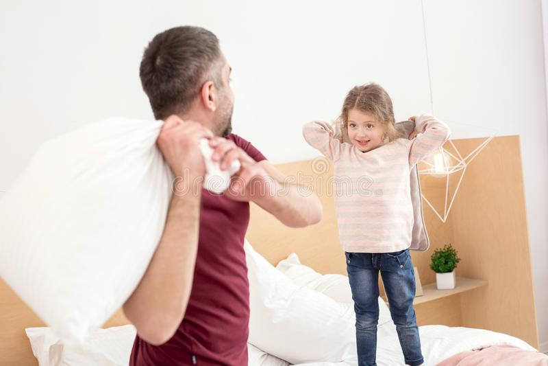 Glad pappa och flicka som har en kuddestrid royaltyfri fotografi