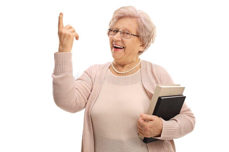 Glad pensionär som pekar upp med hennes finger royaltyfria foton