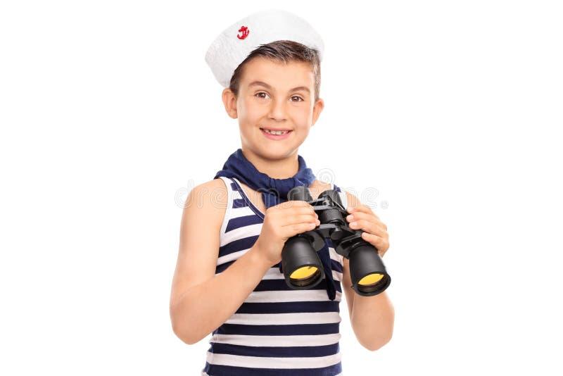 Glad pojke i en sjömandräkt som rymmer ett par av kikare royaltyfri bild