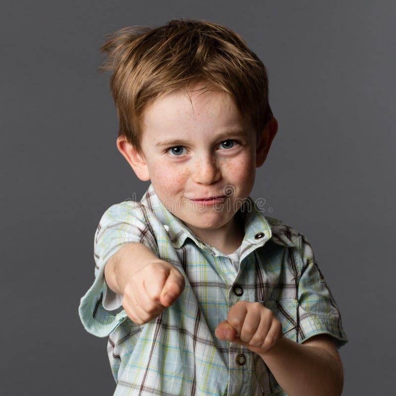 Glad pojke med fräknar som spelar som en toppen hjälte arkivbilder