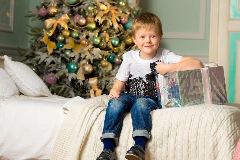 Glad pojke med gåvor nära ett dekorerat träd nytt år arkivfoto