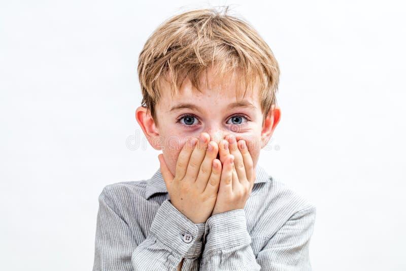 Glad pojke som är hållande tillbaka från bristning ut av att skratta för osäkerhet fotografering för bildbyråer