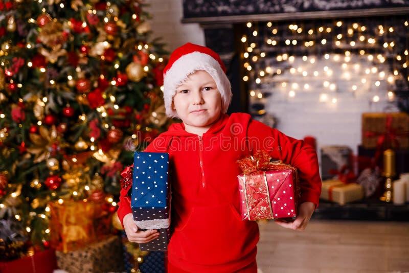 Glad pojke som kläs som Santa Claus med gåvor för jul royaltyfri bild