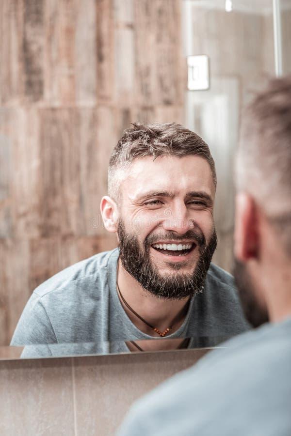Glad positiv man som ler till hans reflexion royaltyfri bild