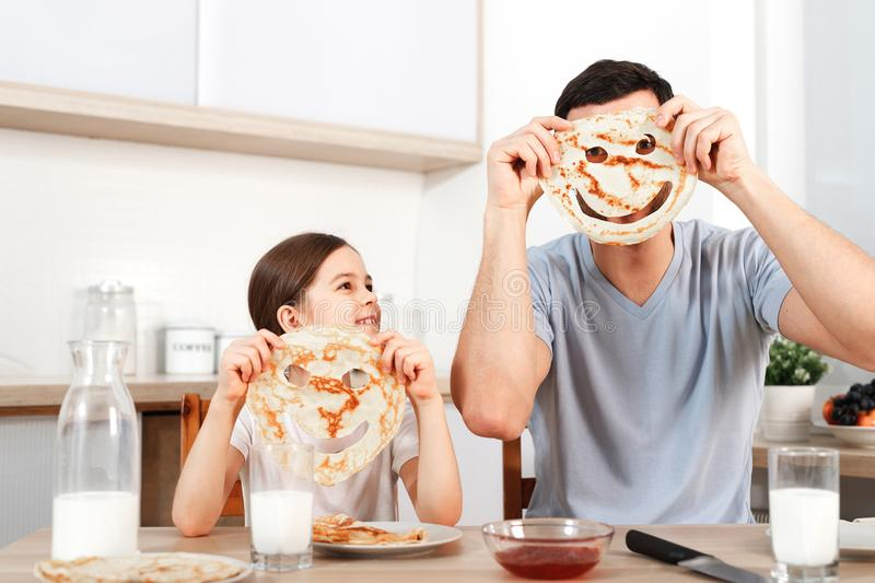 Glad positive young father foolishes with her small daughter at kitchen, make faces from pancakes, have tasty breakfast royalty free stock image