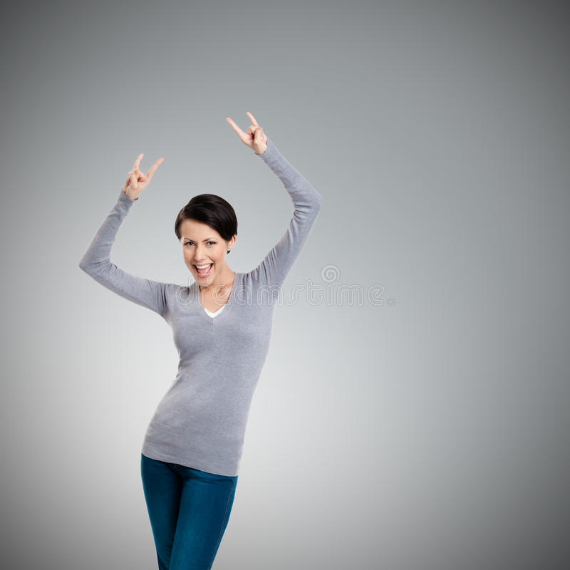 Glad pretty woman puts her hands up with two fingers pointed up stock image