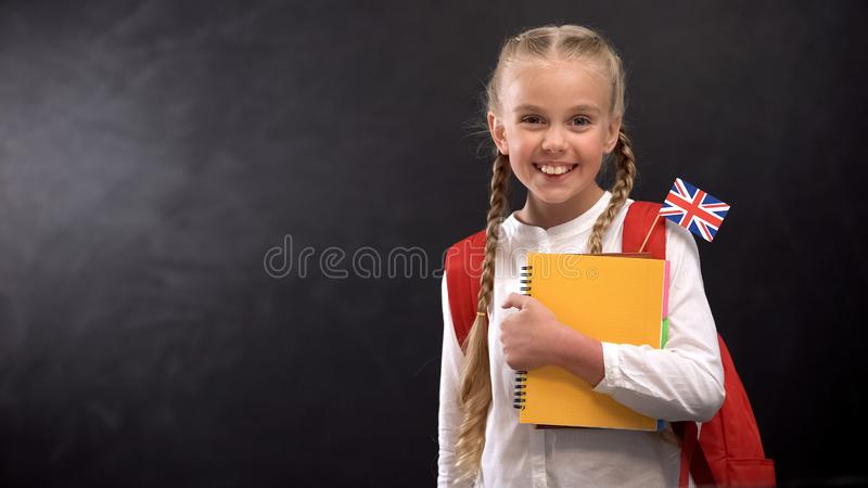 Glad pupil holds books with Great Britain flag, ready to learn foreign language. Stock photo royalty free stock photos