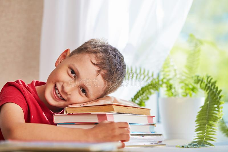 Glad pys som sitter på tabellen med blyertspennor och läroböcker Lycklig barnelev som gör läxa på tabellen royaltyfria foton