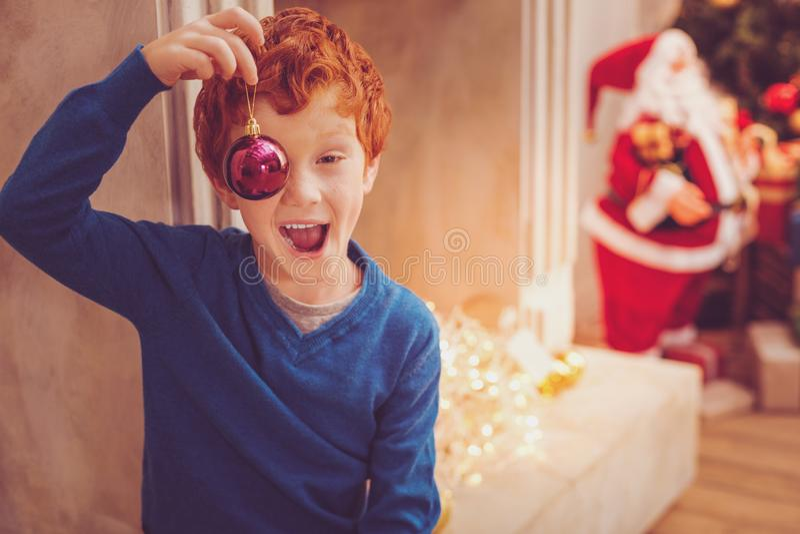 Glad rödhårig pojke som täcker hans öga med en julstruntsak royaltyfria foton