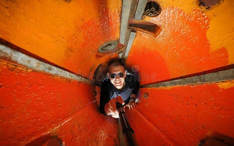Glad Selfie ung grabb med exponeringsglas i torpedrummet av en ubåt Målat i apelsin, begreppet av begränsat utrymme, arkivfoton