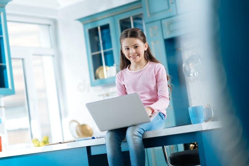 Glad skolflicka som arbetar på hennes bärbar dator arkivbild