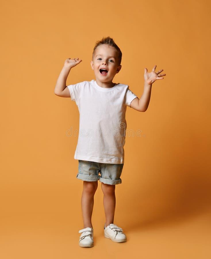 Glad skrikande pojke i vit t-shirt, blå jeans shorts och vita sensorer som skriker med händerna på gula royaltyfri bild