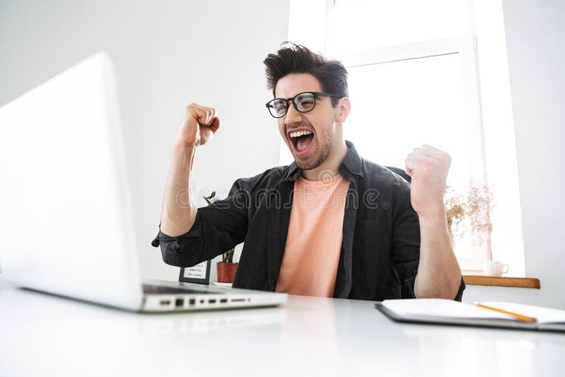 Glad skrikig stilig man i glasögon genom att använda bärbar datordatoren fotografering för bildbyråer