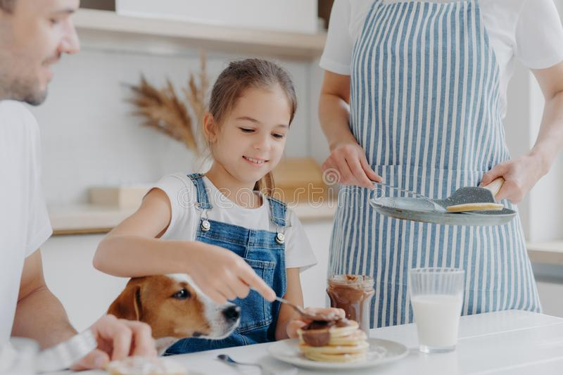 Glad small girl enjoys eating tasty dessert prepared by mum, adds melted chocolate to pancakes, enjoys being together and mother, stock images