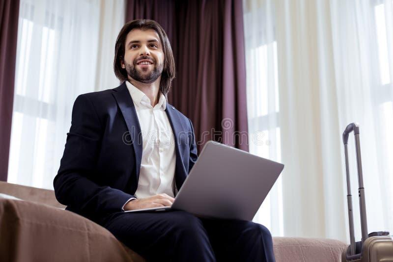 Glad smart stilig entreprenör som sitter på sängen royaltyfri fotografi