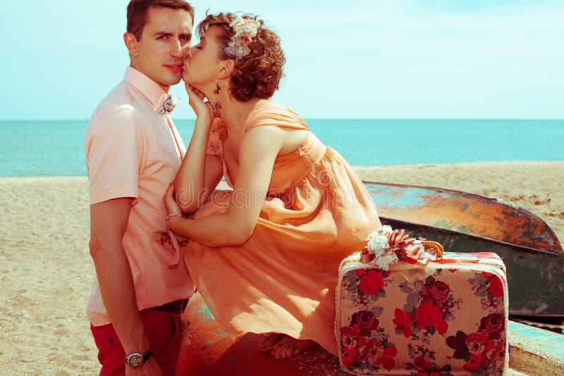 Glad smekmånskoncept Unga gifta par hipsters i trendiga kläder som kysser på stranden Sunny sommardag arkivbilder