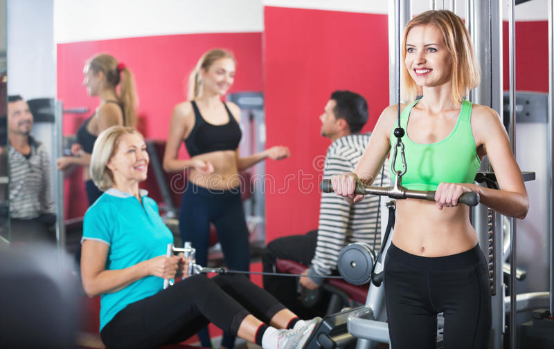 Glad smiling people weightlifting training in health club royalty free stock images