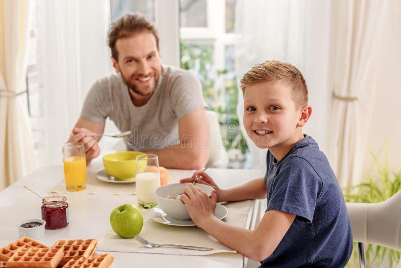 Glad son som äter sädesslag med hans pappa arkivbilder