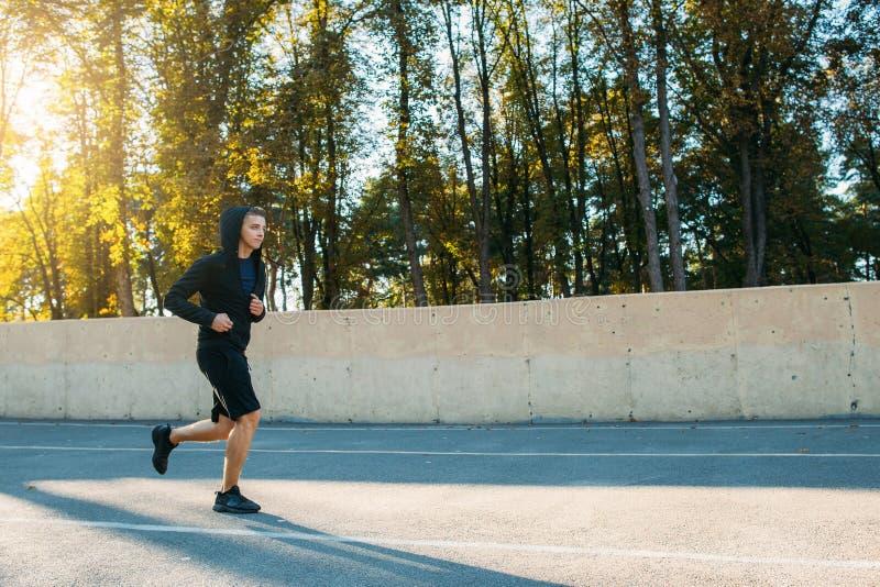Glad sportsman running on stadium stock images